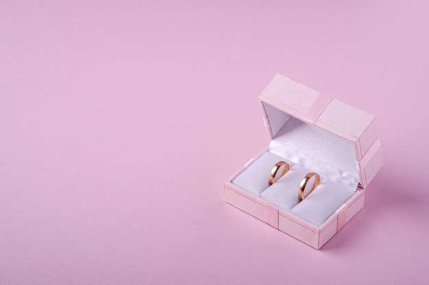 Fedi nuziali in contenitore di regalo rosa su fondo rosa molle, vista di angolo, spazio della copia