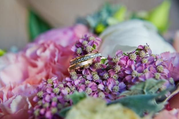 Fedi nuziali in oro con diamanti sul bouquet della sposa.