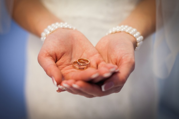 Fedi nuziali nelle mani della sposa. la ragazza si offre di sposarsi