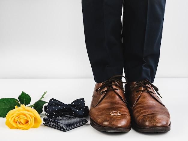 Fedi nuziali, rose, gambe da uomo