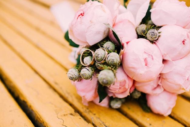 Fedi nuziali su un bouquet di peonie