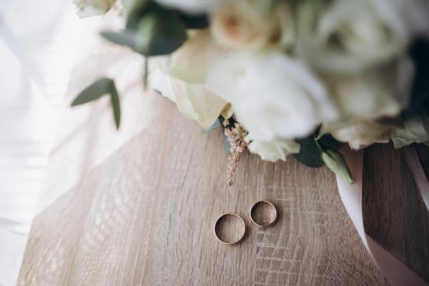 Fedi nuziali su un mazzo di fiori bianchi e rosa.