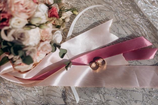 Fedi nuziali sui fiochi nastri rosa e tenero bouquet di nozze