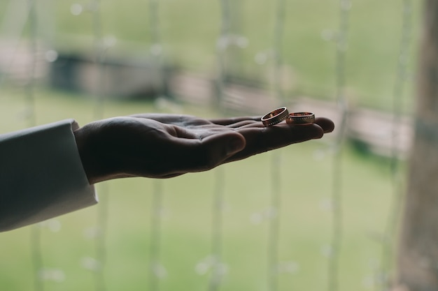 Fedi nuziali sul palmo del primo piano dello sposo