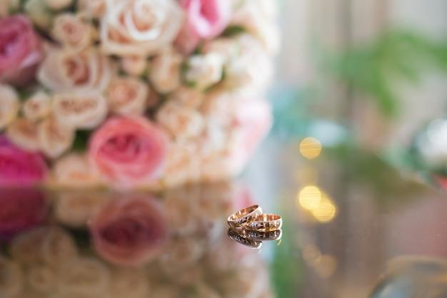 Fedi nuziali sul tavolo con un mazzo di fiori
