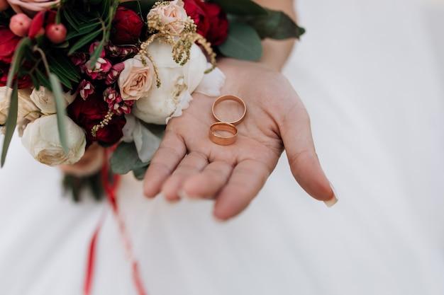 Fedi nuziali sulla mano della donna, bouquet da sposa di fiori rossi e bianchi, dettagli del matrimonio