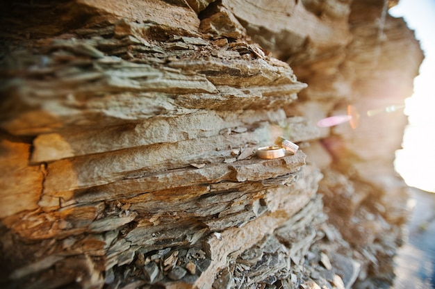 Fedi nuziali sulla pietra di roccia sul tramonto