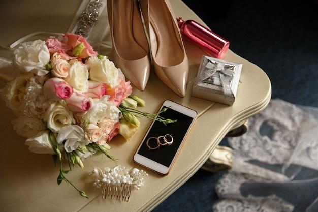 Fedi nuziali sullo smart phone vicino alla scatola dell'anello, scarpe nuziali sui tacchi alti, bottiglia di profumo rosa vicino al mazzo di nozze