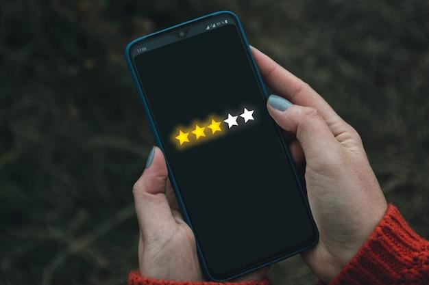 Feedback, revisione e aumento della bandiera del concetto di valutazione. l'utente del telefono digitale offre stelle nella sua recensione e feedback.