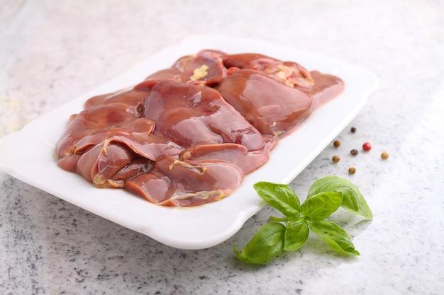 Fegato crudo di pollo in un piatto bianco su sfondo bianco