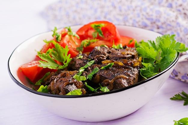 Fegato di manzo arrosto o grigliato con insalata di cipolle e pomodori, cucina mediorientale.