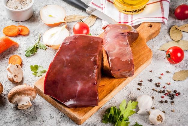Fegato di manzo crudo con spezie, erbe e verdure, tavolo in pietra grigia