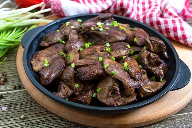 Fegato di pollo fritto con giovani cipolle verdi in una padella di ghisa o. gustoso piatto salutare
