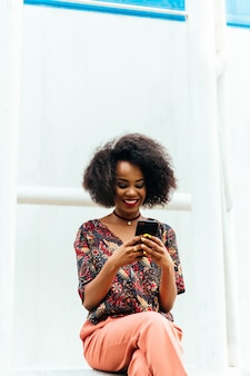 Felice affascinante donna afro-americana, guardando lo schermo smartphone, sorridendo allegramente
