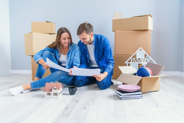 Felice allegra coppia in amore divertendosi insieme nel loro nuovo appartamento dopo aver rimosso le scatole di cartone