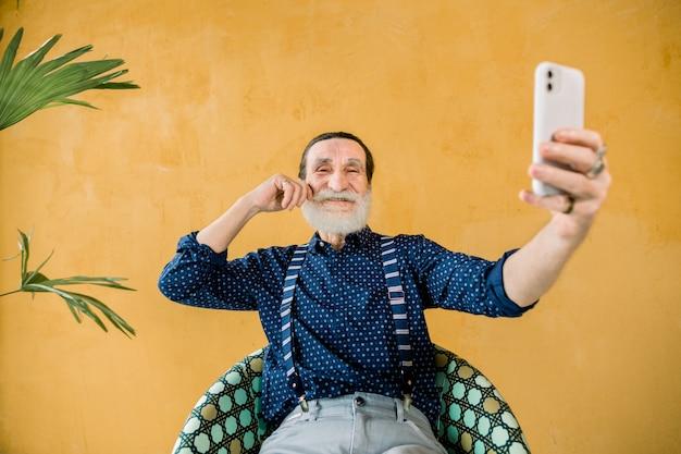 Felice allegro bello maturo uomo hipster maturo con barba grigia, indossa eleganti abiti alla moda, tenendo il suo smartphone per fare selfie foto, seduto su sfondo giallo isolato