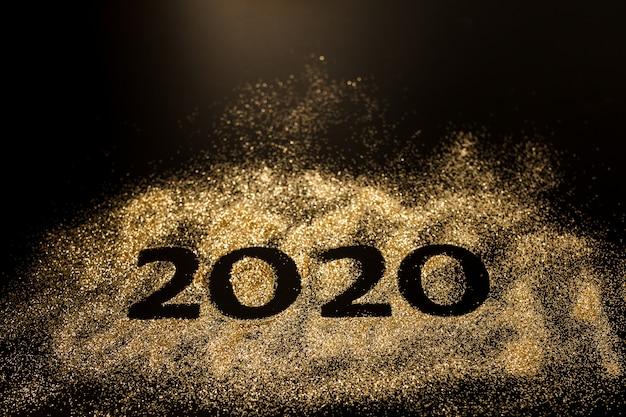 Felice anno nuovo 2020. collage creativo di numeri due e zero costituiva l'anno 2020. bellissimo scintillante numero d'oro 2020 su nero