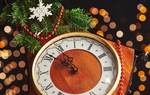 Felice anno nuovo a mezzanotte, vecchio orologio in legno con luci natalizie e rami di abete