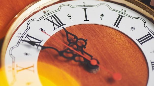 Felice anno nuovo a mezzanotte, vecchio orologio in legno con luci natalizie