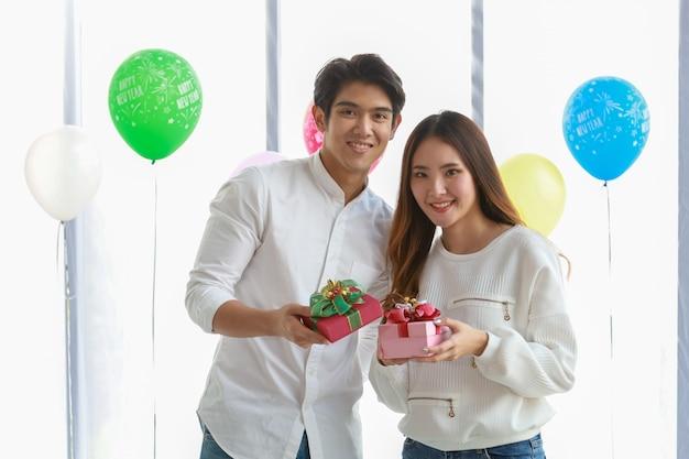 Felice anno nuovo e concetto di coppia. il giovane asiatico e la donna sorridono e tengono il contenitore di regalo sveglio nel partito.