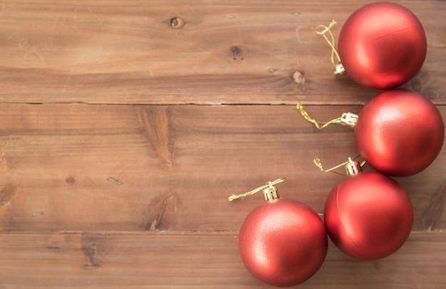 Felice anno nuovo e concetto di natale. vista piana di disposizione della palla rossa dell'ornamento sulla vecchia plancia di legno con lo spazio della copia per testo.