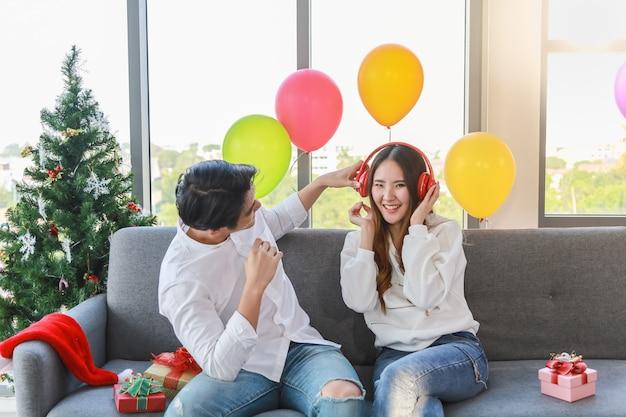 Felice anno nuovo, natale e concetto di coppia. il giovane e la donna asiatici ascoltano musica con la cuffia rossa e la seduta sul sofà con il contenitore di regalo nella festa di natale