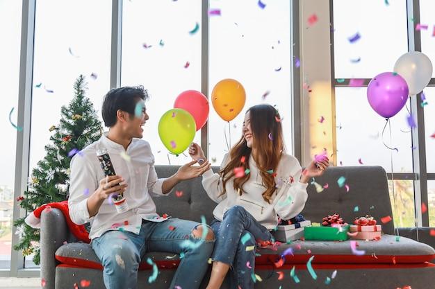 Felice anno nuovo, natale e coppia celebrano il concetto. il giovane e la donna asiatici sorridono e ridono con il tiro di carta dei coriandoli e sedersi sul sofà con il contenitore di regalo e l'aerostato variopinto nella festa di natale