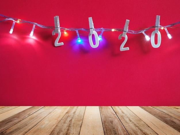 Felice anno nuovo. piano d'appoggio di legno e numero di legno 2020 che appendono sopra il fondo rosso della parete con copyspace.