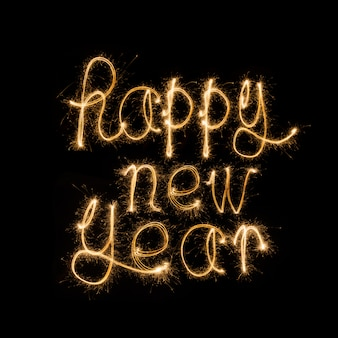 Felice anno nuovo scritto con i fuochi d'artificio sparkle
