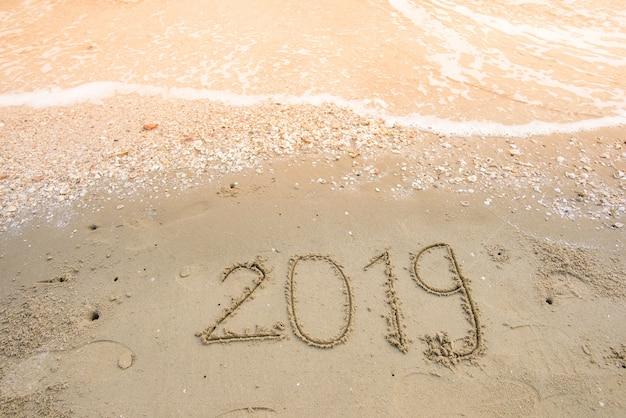 Felice anno nuovo su sfondo di sabbia