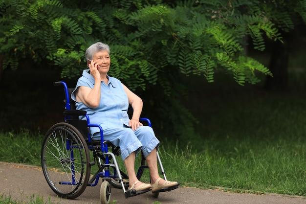 Felice anziana donna disabile seduta in sedia a rotelle all'aperto parlando al telefono