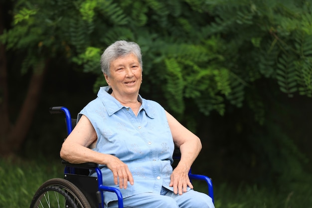 Felice anziani disabili donna seduta in sedia a rotelle all'aperto