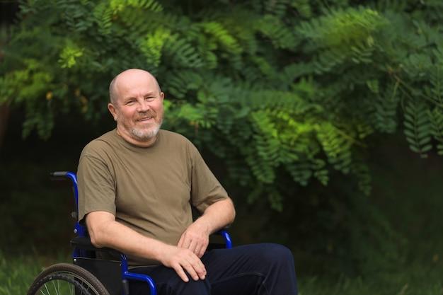 Felice anziani disabili uomo seduto in sedia a rotelle all'aperto