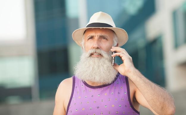 Felice anziano uomo barbuto turista sorridente e ridacchiando mentre si utilizza il telefono cellulare