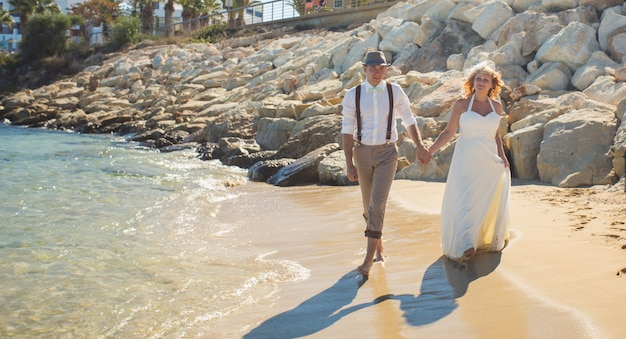 Felice appena sposato giovani sposi celebrando e divertirsi in bellissima spiaggia