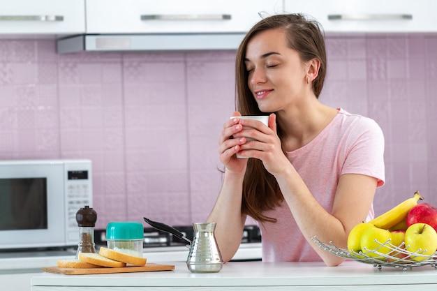 Felice, attraente, la donna beve e gusta un caffè caldo e gustoso per la colazione al mattino presto in cucina a casa