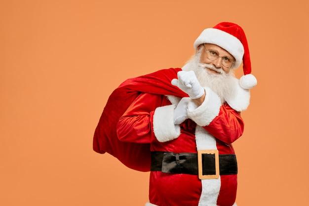 Felice babbo natale che porta sulla grande borsa rossa piena di regali