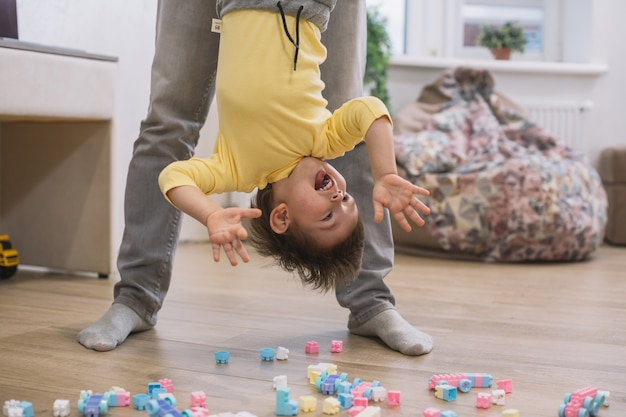 Felice bambino a testa in giù giocando