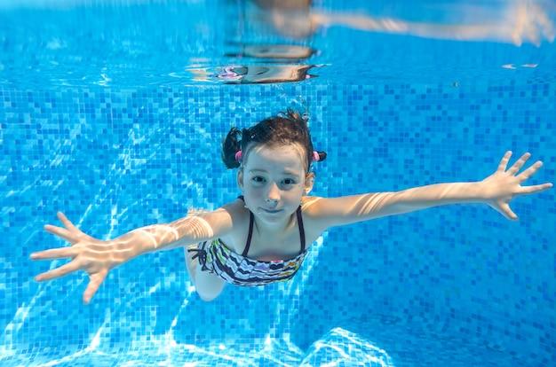 Felice bambino attivo nuota sott'acqua in piscina