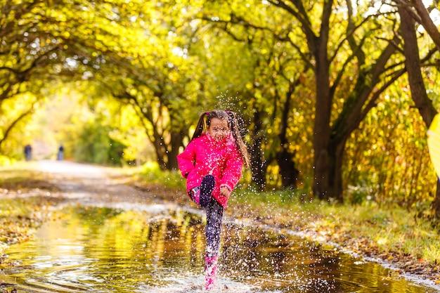 Felice bambino divertente che salta sulle pozzanghere in stivali di gomma e ridendo