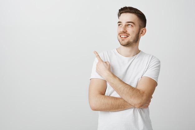 Felice bel giovane in maglietta bianca che punta il dito nell'angolo superiore sinistro