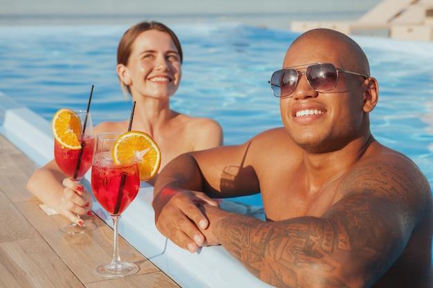 Felice bell'uomo africano e la sua ragazza di relax in piscina, godendo le loro vacanze estive. mare, resort, concetto di hotel