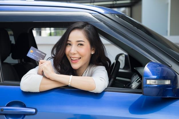 Felice bella donna asiatica seduta all'interno della nuova auto blu e mostrando la carta di credito paga per l'olio, paga una gomma, manutenzione in garage, effettua il pagamento per il rifornimento di carburante auto alla stazione di benzina, finanziamento automobilistico