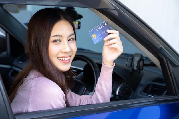 Felice bella donna asiatica seduta all'interno della nuova auto blu e mostrando la carta di credito paga per olio, paga una gomma, manutenzione in garage, effettua il pagamento per il rifornimento di carburante auto alla stazione di benzina, finanziamento automobilistico