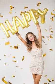 Felice bella donna che celebra il nuovo anno in coriandoli dorati