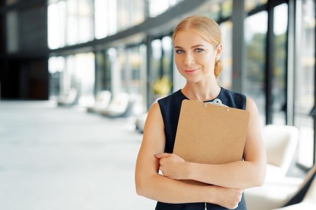 Felice bella donna d'affari con appunti in ufficio.