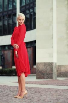 Felice bella donna in abito estivo rosso