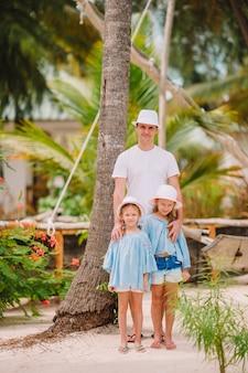 Felice bella famiglia di papà e bambini sulla spiaggia bianca