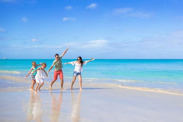 Felice bella famiglia di quattro persone sulla spiaggia