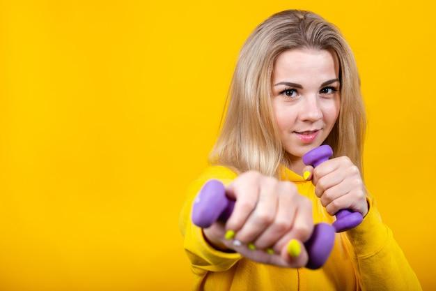 Felice bella giovane donna bionda in abiti sportivi gialli casual facendo esercizi con manubri viola piccoli 0,5 kg.